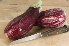 Aubergines or eggplants. Two purple and white aubergines or eggplants on a wooden board Stock Image