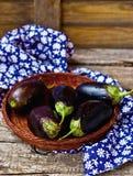 Aubergines fraîches et organiques dans un panier wattled Photographie stock