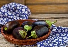 Aubergines fraîches et organiques dans un panier wattled Photographie stock libre de droits