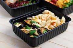 Aubergines frites dans le conteneur avec les ailes et les légumes crus de poulet grillés sur le fond rustique, la tomate-cerise e image stock