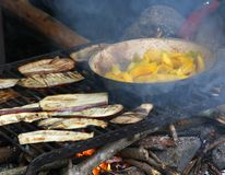 Aubergines and peppers cooked in a barbecue outdoors Stock Image