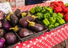Aubergines pourpres et rouge et poivrons verts sur la table couverte de nappe rouge et blanche de polkadot photos stock