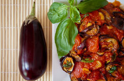 Aubergines in tomato sauce, detail. Platter of grilled aubergines  in a tomato sauce with basil and a whole aubergine on the side Royalty Free Stock Image
