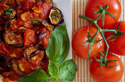 Aubergines in tomato sauce, detail. Platter of grilled aubergines in a tomato sauce with basil and tomatoes on the side. Close-up detail Stock Images