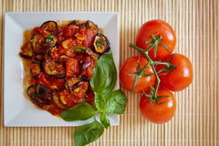 Aubergines in tomato sauce with fresh tomatoes. Platter of grilled aubergines  in a tomato sauce with basil and tomoatoes on the vine on the side Royalty Free Stock Photography