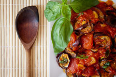 Aubergines in tomato sauce with wooden spoon. Platter of grilled aubergines  in a tomato sauce with basil and wooden spoon on the side Stock Images