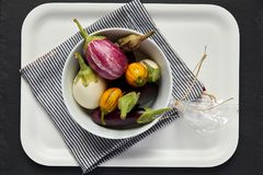 Aubergines in White Bowl on Tray. Multicolored Aubergines in White Bowl on black striped dishtowel Royalty Free Stock Images