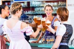 Aubergiste et invités buvant de la bière en Bavière Image stock