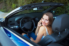 Сaucasian woman talking on phone in a cabriolet car Stock Photography
