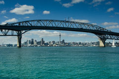 Auckland - The City of Sails. Auckland city skyline seen from under the harbour bridge with with a sailboat yacht sailing under the arches. Set under blue sky royalty free stock photo