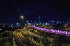Auckland huvudväg på natten och stadshorisont royaltyfri fotografi