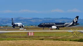 Air New Zealand Airbus A320 in All Blacks livery taxiing as sister aircraft lands at Auckland International Airport. AUCKLAND, NEW ZEALAND - DECEMBER 17: Air New Royalty Free Stock Images