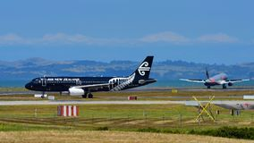 Air New Zealand Airbus A320 in special All Blacks livery taxiing as rival Jetstar Airbus A320 lands at Auckland International Airp. AUCKLAND, NEW ZEALAND Royalty Free Stock Photo