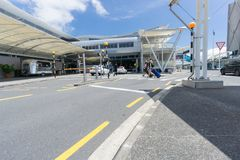 People arriving at airport to depart. AUCKLAND, NEW ZEALAND - NOVEMBER 23, 2017 People including young couple pulling suit cases crossing road towards entranance Royalty Free Stock Photos