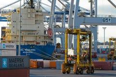 AUCKLAND, NOVA ZELÂNDIA - 17 DE ABRIL: Embarcação, portadores de straddle, guindastes rodados e pilha de recipientes no porto mar Fotografia de Stock Royalty Free