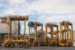 AUCKLAND, NUEVA ZELANDA - 2 DE ABRIL DE 2012: 4 carretillas puente y pilas de envases en el puerto Foto de archivo libre de regalías