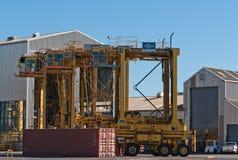 AUCKLAND, NUEVA ZELANDA - 2 DE ABRIL DE 2012: 4 carretillas puente y pilas de envases en el puerto Imagen de archivo libre de regalías