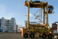 AUCKLAND, NUOVA ZELANDA - 17 aprile 2012: Carrello a portale e pila di contenitori a porto marittimo Immagine Stock