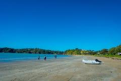 AUCKLAND NYA SJÄLLAND MAY 12, 2017: Vit sandstrand på den Waiheke ön, Nya Zeeland med en härlig blå himmel i a Royaltyfri Bild