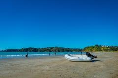 AUCKLAND NYA SJÄLLAND MAY 12, 2017: Vit sandstrand på den Waiheke ön, Nya Zeeland med en härlig blå himmel i a Royaltyfria Bilder