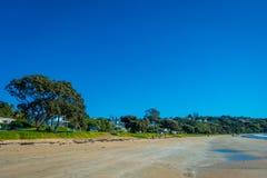 AUCKLAND NYA SJÄLLAND MAY 12, 2017: Vit sandstrand på den Waiheke ön, Nya Zeeland med en härlig blå himmel i a Royaltyfria Foton