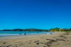 AUCKLAND NYA SJÄLLAND MAY 12, 2017: Vit sandstrand på den Waiheke ön, Nya Zeeland med en härlig blå himmel i a Arkivfoton