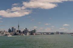 Auckland skyline downtown and Westhaven. Auckland, New Zealand - March 3, 2017: City skyline with Westhaven and beyond seen from greenish ocean water under blue Royalty Free Stock Photos