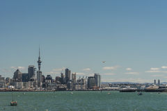 Auckland skyline downtown and Westhaven. Auckland, New Zealand - March 3, 2017: City skyline with Westhaven and beyond seen over greenish ocean water under blue Royalty Free Stock Photo