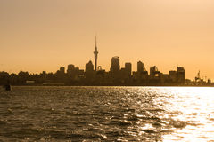 Auckland Skyline at Sunset. Auckland city skyline seen from the Waitemata Harbour as the sun sets in the west. Set under golden hour sky the city in the centre Stock Photo