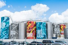 Auckland tank farm art storage tanks painted. AUCKLAND, NEW ZEALAND - DECEMBER 27, 2017; tank farm, industrial storage tanks holding chemicals decorated in royalty free stock images