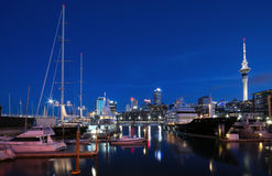 Auckland Viaduct Harbour. Wide view of Auckland Harbour at sunset with clear bule sky and city skyline buildings lit up. various yachts and launches fill the royalty free stock photos