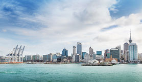 Auckland view at the noon. Skyline of Auckland with city central business district and port cranes at cloudy noon stock images