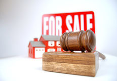 At an auction. House auction concept shot with a sign, home and gavel Royalty Free Stock Image