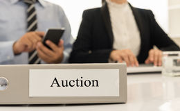Auction. Closeup auction file with  two business person bidding via electronic industries in background Stock Photo