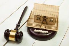 auction gesetz Miniaturhaus auf Holztisch und Gerichts-Hammer lizenzfreie stockfotos