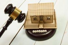 auction gesetz Miniaturhaus auf Holztisch und Gerichts-Hammer lizenzfreies stockbild