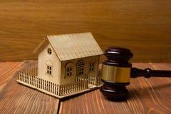 auction gesetz Miniaturhaus auf Holztisch und Gerichts-Hammer lizenzfreie stockbilder