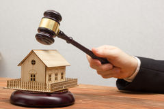 Auction, Real Estate concept. Hand with judge gavel and house model.  Stock Photo