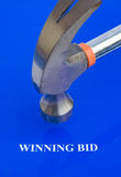 Auction; the winning bid. Winning bid in bold white letters with the hammer coming down to confirm the deal. The image is isolated on a plain blue background stock photography