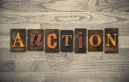 Auction Wooden Letterpress Theme. The word AUCTION theme written in vintage, ink stained, wooden letterpress type on a wood grained background Stock Photos