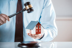 Auctioneer knocking down a property sale. Holding a model house as he raises his gavel, or a lawyer or judge mediating in a property dispute in court Royalty Free Stock Photos
