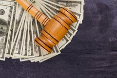 The auctioneer`s hammer on dollar bills. Wooden auctioneer`s hammer lies on fan-lined dollar bills. View from above. Place for the inscription Stock Image