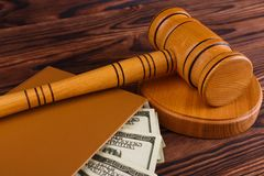 An auctioneer`s hammer on a round stand, a notepad in which there are a lot of dollar bills. A wooden auctioneer`s hammer on a round stand, a brown notepad in Stock Photos