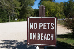 Aucun animaux familiers sur le signe de Brown de plage Photographie stock libre de droits