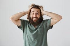 Aucune manière, je suis devenu chanceux Portrait de type oriental heureux et choqué avec la barbe tenant des mains sur la tête et Photographie stock libre de droits