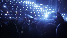 A audiência com mãos aumentou em um festival e nas luzes de música que fluem para baixo de cima da fase Muitos povos com vídeos de arquivo