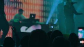 A audiência com mãos aumentou em um festival e nas luzes de música que fluem para baixo de cima da fase fundo blured filme