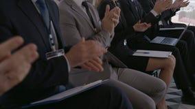 A audiência do negócio aplaude no treinamento video estoque