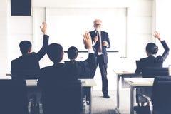 Audiência do negócio que levanta a mão acima quando o homem de negócios falar no treinamento para a opinião com o líder da reuniã imagem de stock royalty free