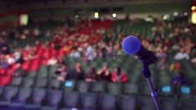 Audiência do seminário da posição do microfone da fase no fundo de fase do auditório, close-up muitos povos que situam em grande video estoque
